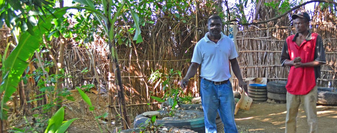 photo of Etienne showing plants at a demo farm