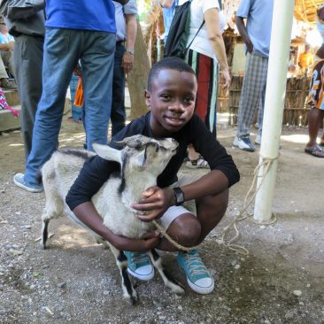 photo of boy and young goat